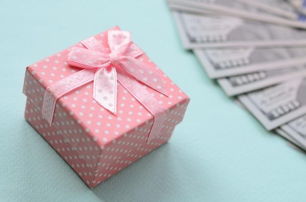 Il contenitore di regalo punteggiato rosa si trova vicino a cento fatture del dollaro