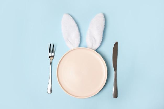 Piatto di pasqua vuoto rosa con orecchie da coniglio su sfondo blu