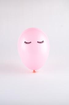 Palloncino viso rosa con ciglia nere occhi chiusi. concetto minimo