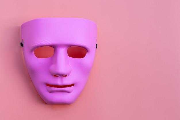 Maschera viso rosa su superficie rosa. copia spazio