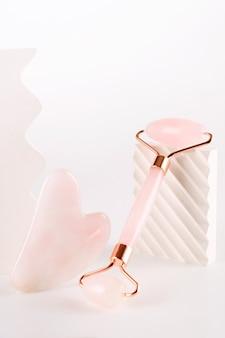Rullo viso rosa e massaggiatore gua sha realizzato in pietra di quarzo naturale su sfondo bianco. trattamento lifting e tonificante a casa.