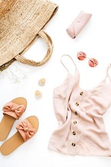 Vestiti femminili rosa e accessori su sfondo bianco. disposizione piatta, vista dall'alto