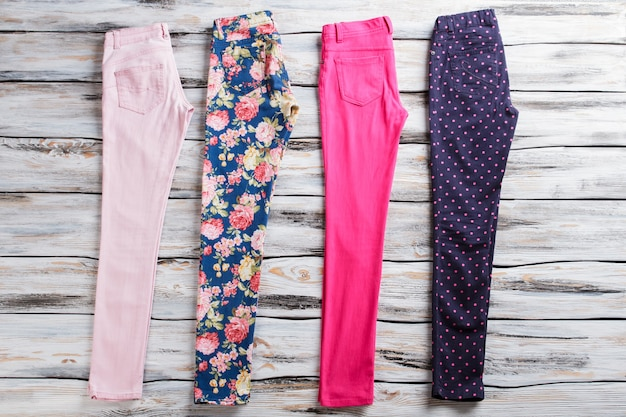 Pantaloni rosa e floreali. pantaloni diversi su fondo in legno. varietà di colori. ultima merce in magazzino.