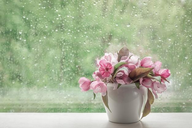 Fiori rosa di melo decorativo in un piccolo vaso bianco su un davanzale.