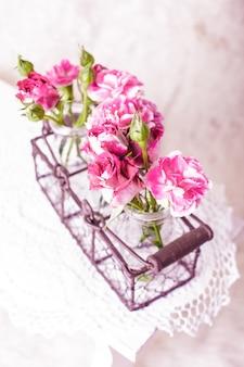 Fiori rosa in bottiglie di vetro in cestino di metallo. concetto di arredamento vintage