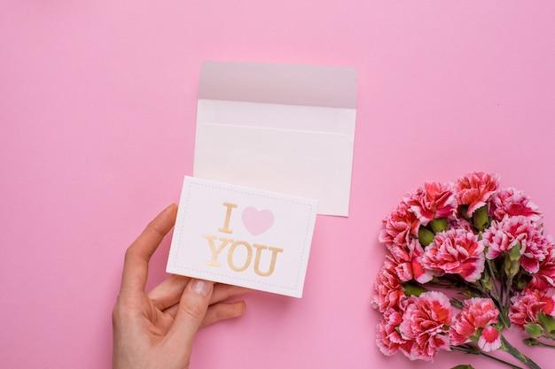 Fiori rosa e mano con la carta ti amo sul rosa