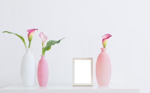 Fiori rosa in vasi e cornice su superficie bianca