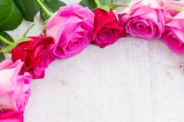 Bordo di fiori di rosa freschi rosa su bianco