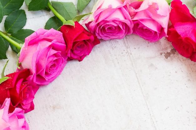 Bordo di rose fresche rosa su bianco