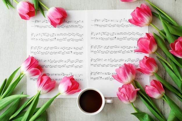 Rosa tulipani freschi su spartiti sul tavolo bianco, vista dall'alto