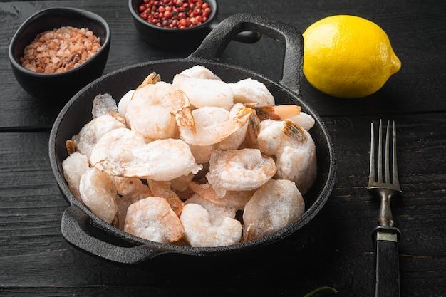 Gamberetti rosa congelati con ghiaccio. set di frutti di mare pelati crudi, in padella o pentola in ghisa, sul tavolo di legno nero