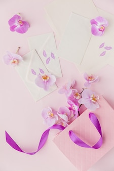 Sacchetto regalo rosa, lettere e fiori di orchidea volanti su superficie rosa chiaro