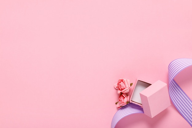 Contenitore di regalo e fiori rosa sul rosa