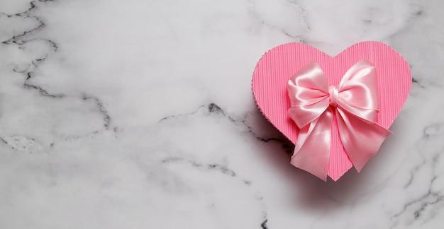 Scatola regalo rosa a forma di cuore su bacground in marmo con formato banner spazio copia