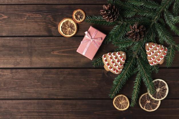 Confezione regalo rosa con coni, rami di abete rosso, biscotti a forma di albero di natale e fette di agrumi secche