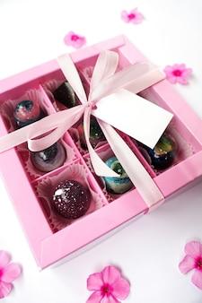 Confezione regalo rosa con cioccolatini fatti a mano su fondo bianco con fiori rosa