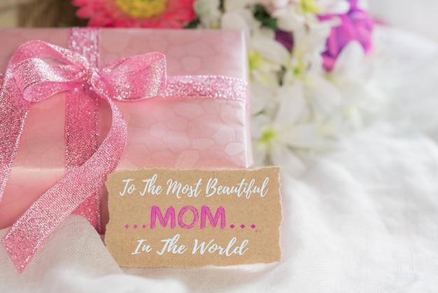 Contenitore di regalo rosa con fiore viola, etichetta di carta su sfondo bianco cheesecloth.