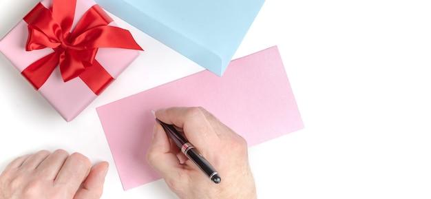 Confezione regalo rosa con fiocco rosso e mani maschili che scrivono lettera d'amore, biglietto di auguri per san valentino o invito a nozze. vista dall'alto. sfondo bianco.