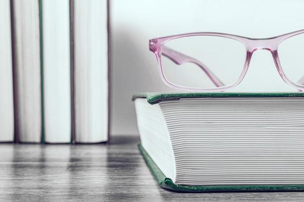 Vetri rosa su un libro spesso in una copertina verde. fila di libri