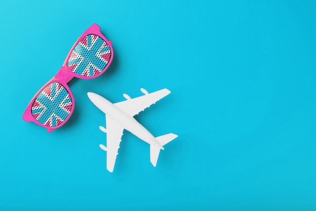 Occhiali rosa con la bandiera del regno unito in lenti su una superficie blu con un aeroplano bianco