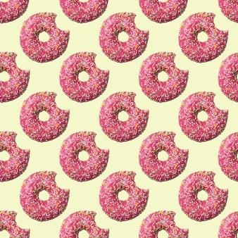 Modello senza cuciture di ciambella morso vetrata rosa su sfondo giallo. cibo di concetto. vista dall'alto.