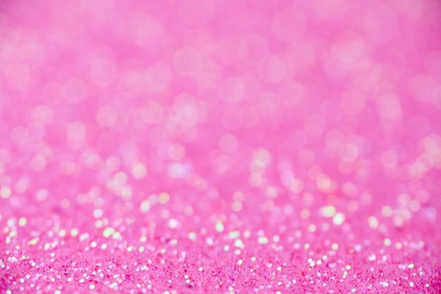 Trama glitter rosa. anno nuovo o sfondo di natale per biglietto di auguri. celebrazione di san valentino. design scintillante brillante per la decorazione festiva: matrimonio, festa o festa di anniversario.