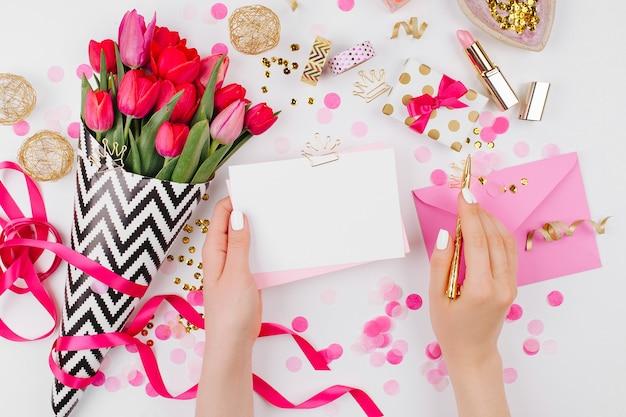 Scrivania in stile rosa e oro con fiori. le mani femminili tengono la carta
