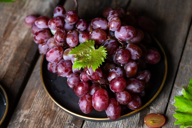 Uva rosa sulla tavola di legno su fondo di legno