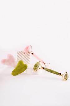 Rullo viso rosa e verde e massaggiatore gua sha realizzato in pietra naturale su sfondo bianco. trattamento lifting e tonificante a casa.