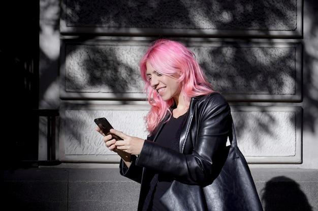 Donna dai capelli rosa vestita di pelle nera che scrive un messaggio sul suo cellulare
