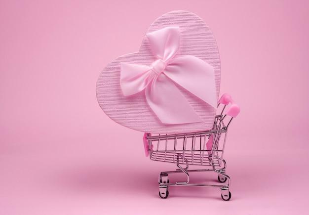 Regalo cuore rosa con fiocco per san valentino nello shopping scart su sfondo rosa, regalo di consegna