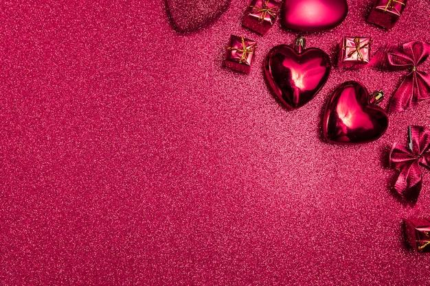 Cuori rosa e regali su sfondo rosa lucido, vista dall'alto
