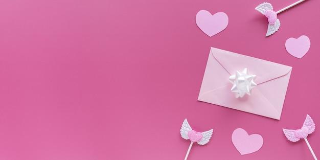 Cuori rosa, toppers, busta con lettera su sfondo rosa. san valentino.