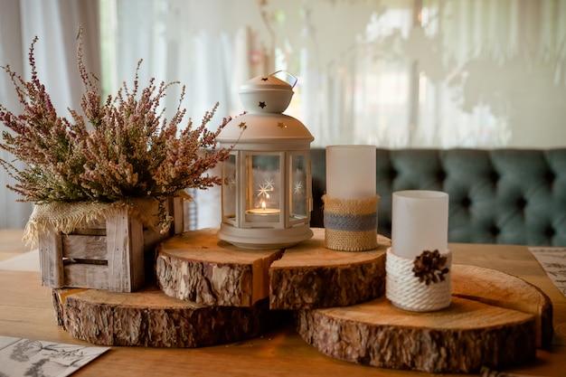 Erica rosa in vaso, candele, lanterna, persiane vintage su sfondo. prepararsi per l'autunno. accogliente set autunnale.