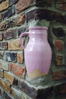 Una brocca rosa all'angolo di un muro di mattoni