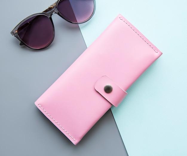 Portafoglio in pelle rosa e occhiali da sole su una superficie grigia e verde