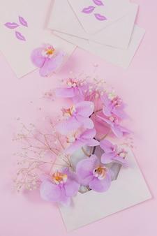 Lettera rosa piena di fiori di orchidea volanti e nuove buste vuote su sfondo rosa chiaro