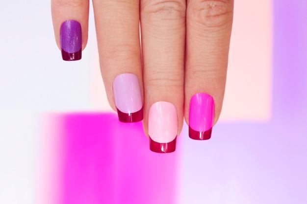 Manicure francese colorato lilla rosa sulla fine della mano femminile.