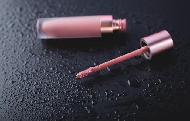 Lucidalabbra rosa su sfondo bagnato