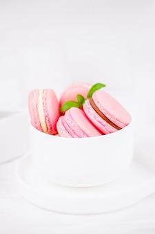 Macarons rosa in tazza bianca