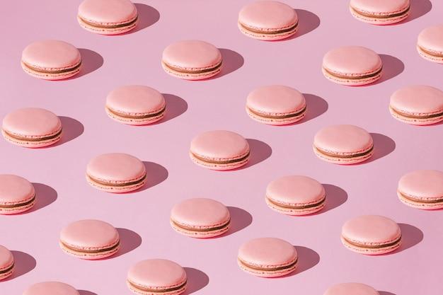 Amaretti rosa con motivo crema al cioccolato con ombre chiare dure su sfondo rosa alla moda