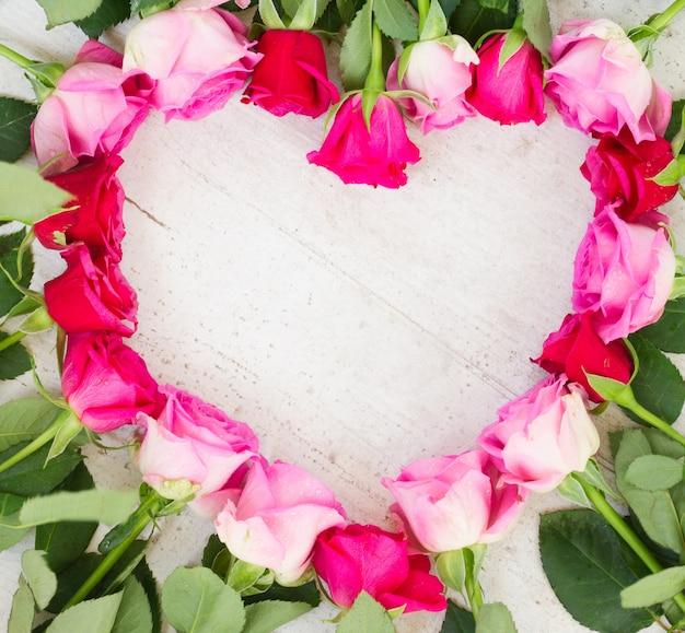Cornice di rose fresche rosa e magenta a forma di cuore su fondo in legno invecchiato