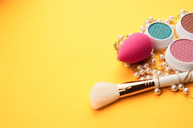 Rosa spugna trucco e polvere pennello sfondo giallo ha ritagliato vista. foto di alta qualità