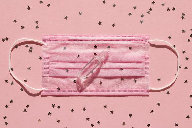 Maschera medica rosa, fiala di vetro trasparente e stelle di coriandoli su uno sfondo rosa.
