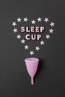 Coppetta mestruale rosa su sfondo nero con con cuore e parole coppa del sonno. prodotto per l'igiene femminile