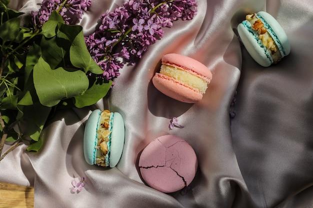 Amaretti francesi rosa e menta o biscotti macarons e fiori lilla su uno sfondo di stoffa. sapori naturali di frutta e bacche, ripieno cremoso per la festa della mamma di san valentino con cibo d'amore.