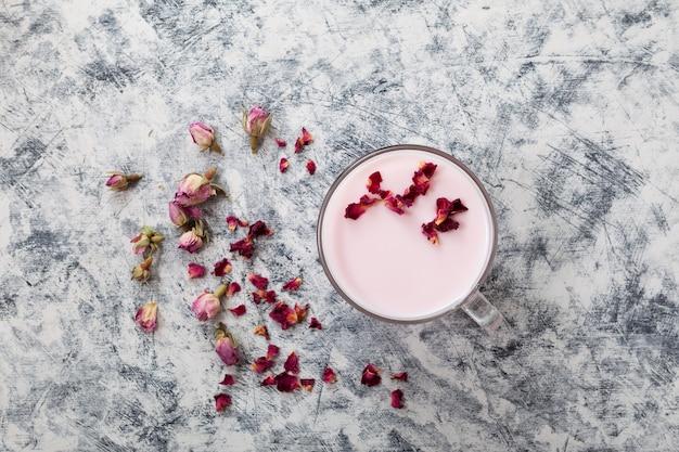 Latte di luna rosa in tazza trasparente vista dall'alto bevanda rilassante di mezzanotte petali di rose essiccate