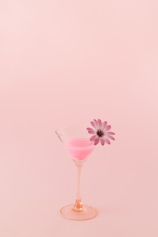 Bevanda al neon rosa cocktail su uno sfondo rosa con un fiore in un bicchiere colori monocromatici
