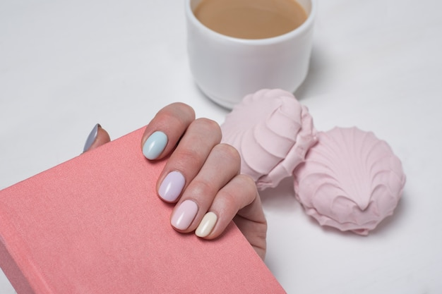 Blocco note rosa in una mano femminile. manicure delicata avvicinamento