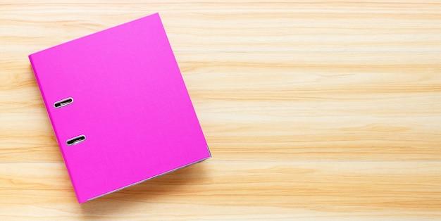 Cartella ufficio rosa su sfondo di legno. vista dall'alto